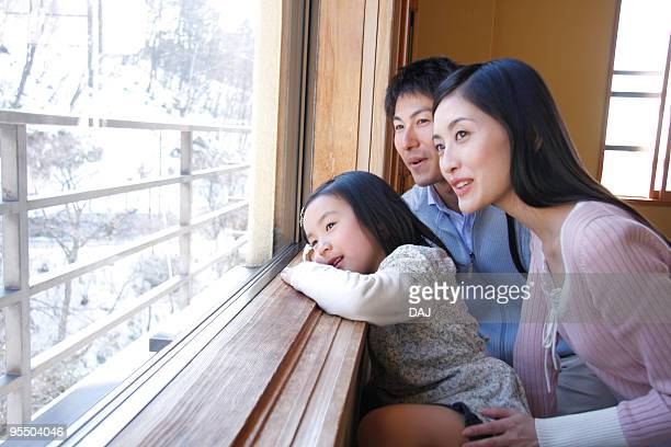 Family looking outside from the window, smiling