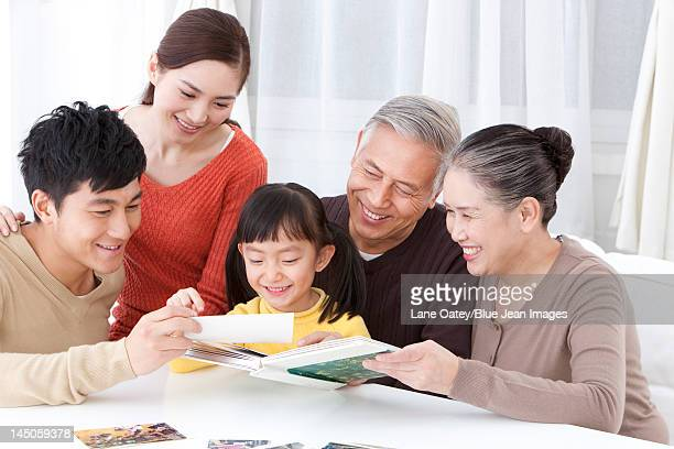 family looking through family album - asian granny pics stock photos and pictures
