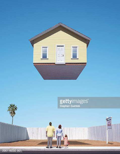 Family looking up at  house floating above empty lot, rear view