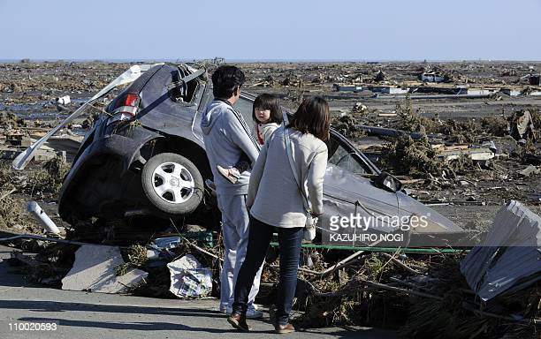 A family looks at a damaged vehicle following a tsunami in the aftermath of a massive 89 earthquake in Minamisoma Fukushima Prefecture on March 12...