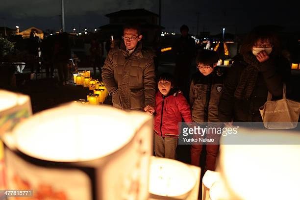 Family looks at paper lanterns during a memorial held in remembrance of victims of the March 11, 2011 earthquake and tsunami at Yuriage Junior High...