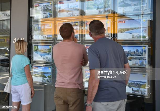 A family looks at properties for sale in a property agents window in Sydney on December 5 2017 Australia's central bank left interest rates at a...