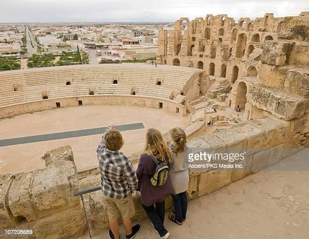 Family looks over Roman colliseum ruins