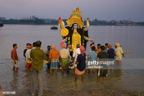 A family lowers a Kali statue to the river at Babu Ghat at the end of the Kali Puja festival During this part of the festival families and...