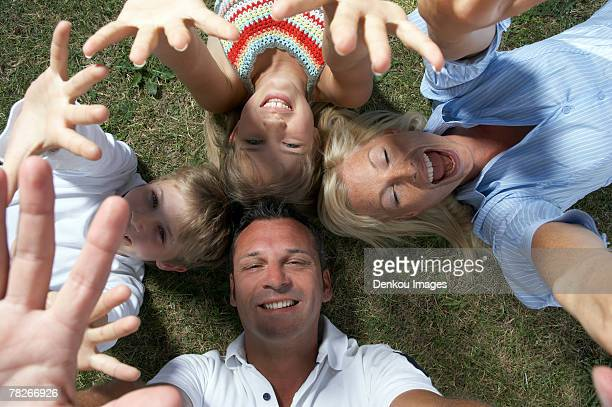 Family lying down on the grass.