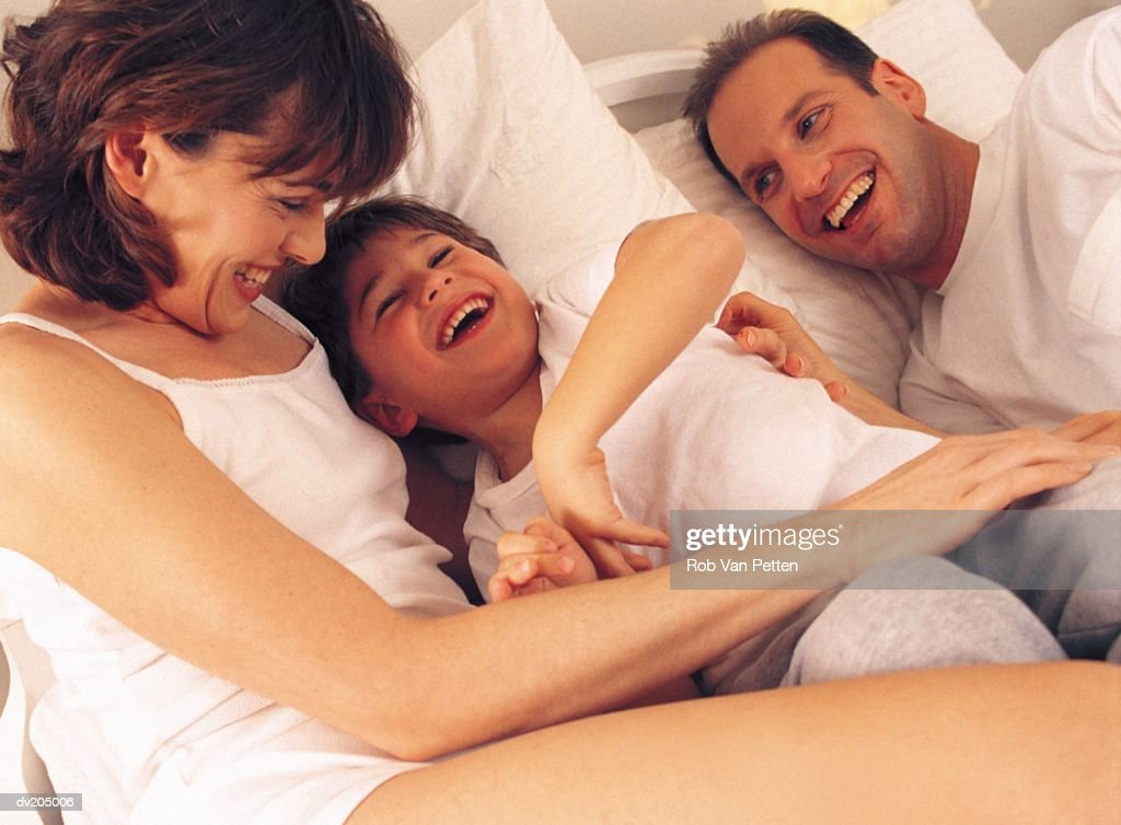 Family lying in bed : Stock Photo