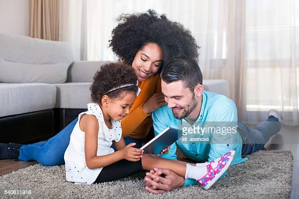 ファミリーに横たわっているカーペットと遊びでゲームをデジタルタブレット
