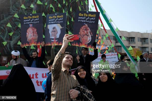 A family makes a selfie with a mobile phone standing in front of banners of Donald Trump and Benjamin Netanyahu and king Salman of Saudi Arabia held...