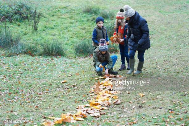 Family making a path out of autumn leaves