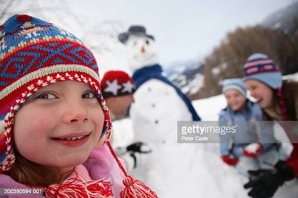 Family making a snow man, girl in foreground smiling