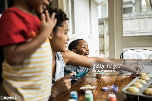 family making cupcakes at birthday party - family stock pictures, royalty-free photos & images