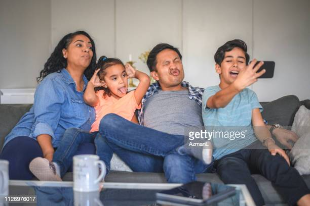 Family making faces while taking selfie at home