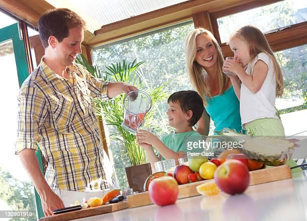 family making fruit smoothies