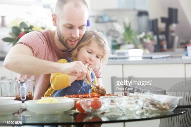 family making homemade pizza - togetherness stock pictures, royalty-free photos & images