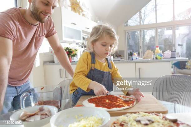 family making homemade pizza - homemaker stock pictures, royalty-free photos & images