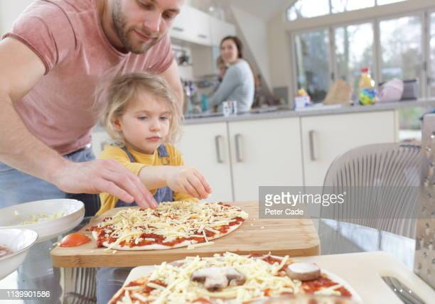 family making homemade pizza - 30 34 years stock pictures, royalty-free photos & images