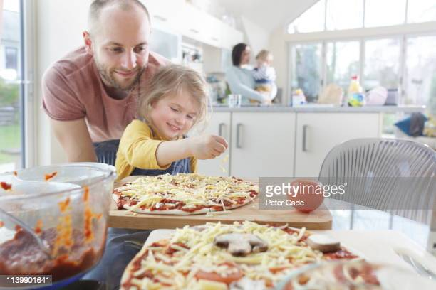 family making homemade pizza - table stock pictures, royalty-free photos & images