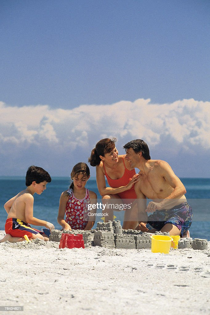 Family making sand castle on the beach : Stockfoto