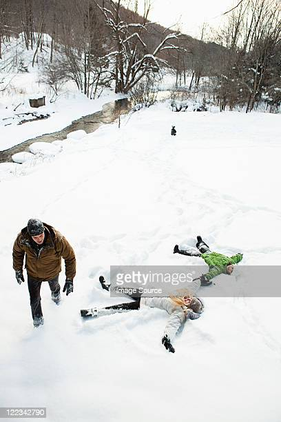 family making snow angels - snow angel stock photos and pictures