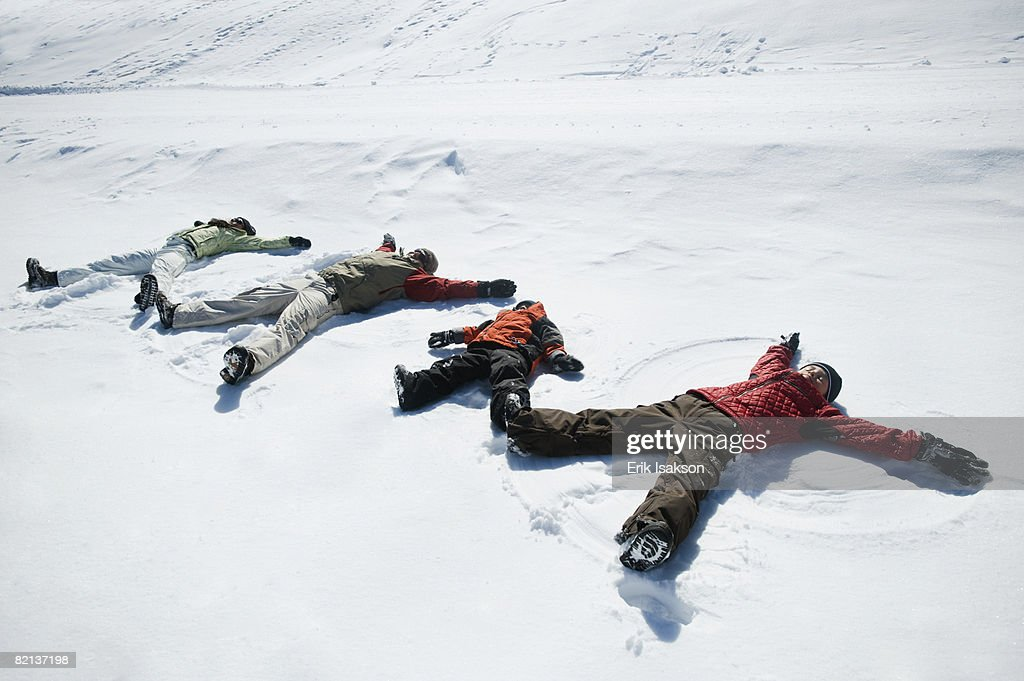 Family making snow angels : Stock Photo