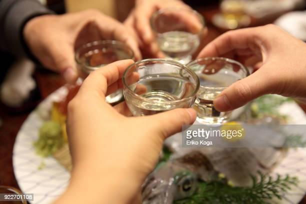 family making toast with sake over sashimi of squid - saki stock photos and pictures