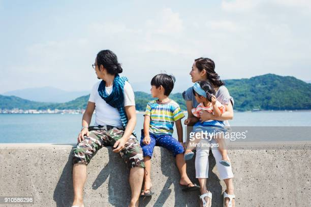 family, man, boy and woman with young girl on her lap sitting side by side on a wall by the ocean. - 週末の予定 ストックフォトと画像