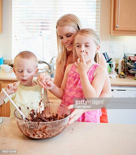 Family melting chocolate in mixing bowl