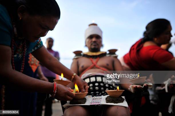 A Family member arranging oil lamps as Nepalese devotee hold oil lamps on their body during the tenth day of Dashain Durga Puja Festival in Bramayani...