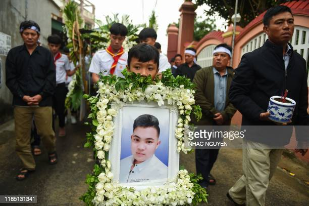 TOPSHOT A family member carries a portrait Hoang Van Tiep during funeral at Dien Chau distritct Nghe An province on November 28 2019 The families of...