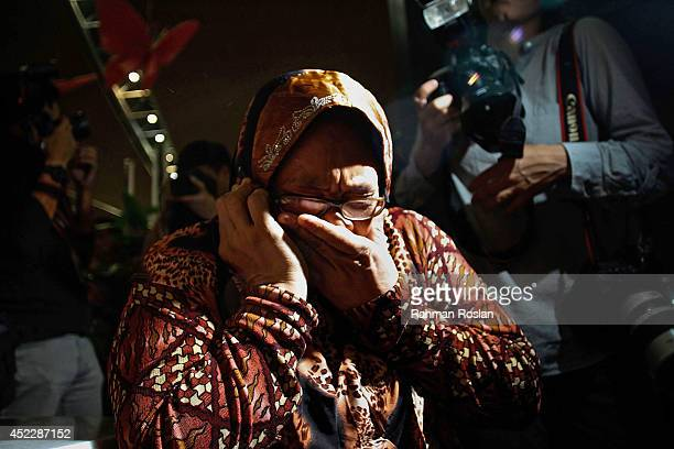 A family member cries as she receives the news of the ill fated flight MH17 on the phone on July 18 2014 in Kuala Lumpur Malaysia Malaysia Airlines...