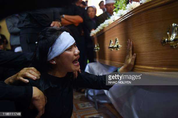 TOPSHOT A family member cries before the coffin bearing the remains of Nguyen Van Hung during a funeral service at a church in Dien Chau district...