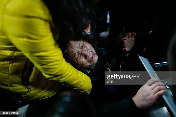 A family member cries on a bench at a hospital where some of the victims of a stampede by new year's revellers were sent in Shanghai on January 1...