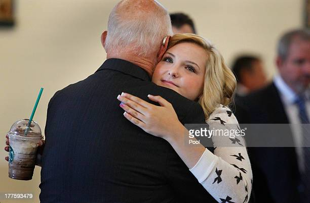 Family member Dave Braun hugs Hannah Anderson at the memorial service for Christina Anderson and Ethan Anderson at Guardian Angels Catholic Church...