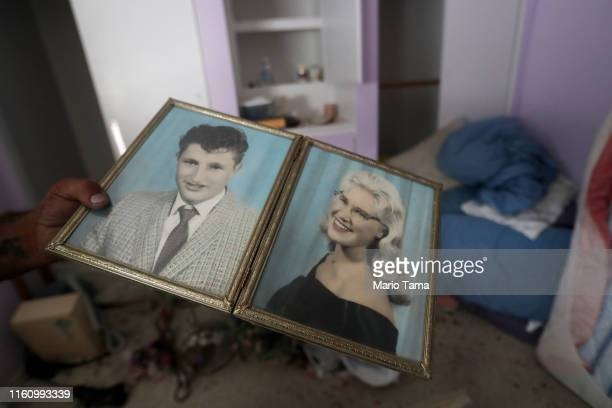 A family member displays old photographs of Benny and Anna Sue Eldridge he found in their home which has been deemed uninhabitable due to structural...