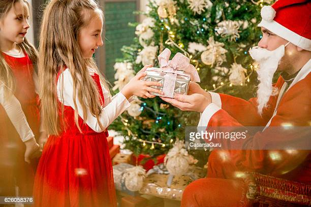Family Member giving Christmas Presents to Little Girls