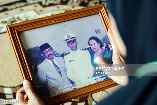 Family member holds a photograph of Marine Colonel Harry Setiawan, commander of the Navy's KRI Nanggala submarine that went missing off the coast of...