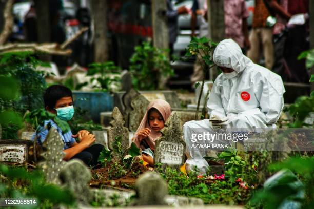 Family member in personal protective equipment suit together with two children pray by the grave of a Covid-19 coronavirus victim who was just...