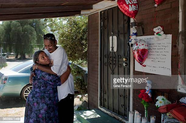 Family member Jeannie Johnsonright gets a hug from a neighbor after putting up a make shift memorial in front of the home where a 2–year–old was...