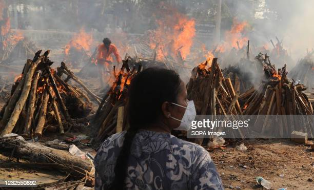 Family member looks on as several funeral pyres of those patients who died of COVID-19 disease burn up during the mass cremation at Ghazipur...