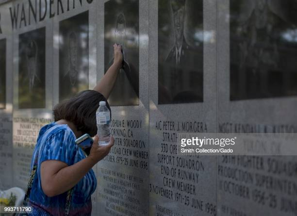 A family member of a 33rd Fighter Wing Khobar Towers victim places her hand on his photo June 25 at Eglin Air Force Base Fla Each year past and...
