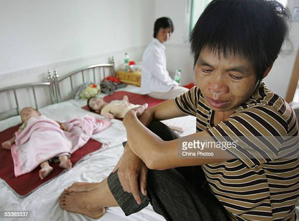 A family member of a miner trapped in a flood at the Daxing Colliery waits for her relative's news at a hospital with her child August 9 2005 in...