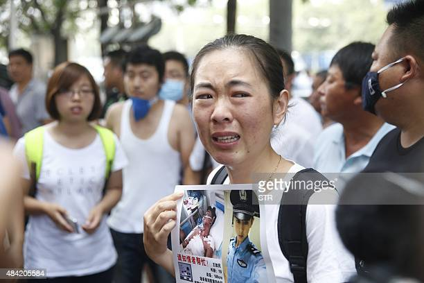 A family member of a missing firefighter from the recent explosions at a chemical warehouse protests outside a hotel where authorities are holding a...
