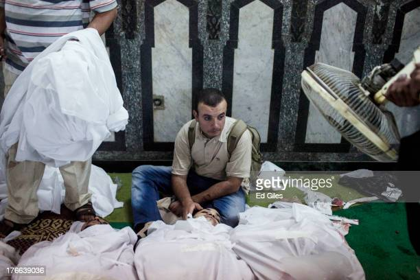 A family member of a supporter of deposed Egyptian President Mohammed Morsi killed during fighting with Egyptian Security Forces sits on the floor of...