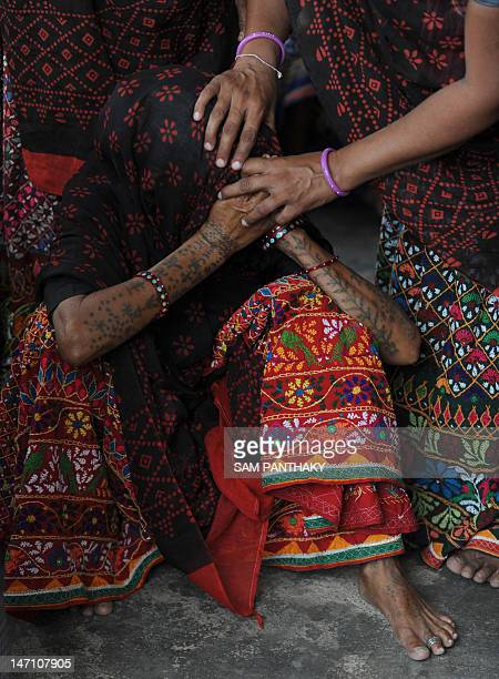 A family member of Mahadev Bharwad is comforted by relatives as she reacts during a Hindu ritual in the village of Kochariya of Bavla Taluka some 40...