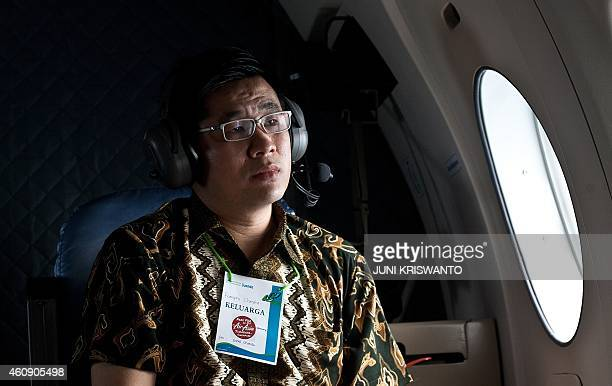 A family member of passengers onboard the missing Malaysian air carrier AirAsia flight QZ8501 gestures while accompanying military personnel on a...