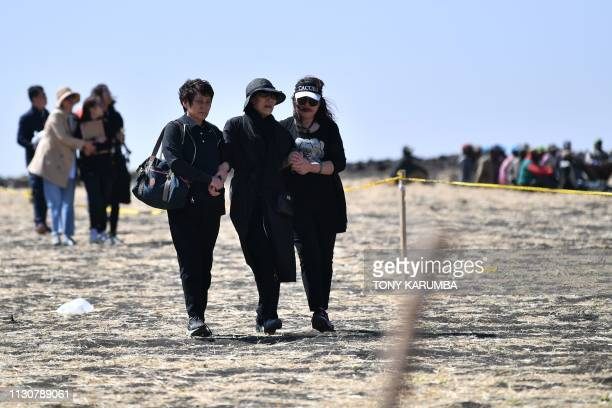 TOPSHOT A family member of victims from China walk toward the crash site of the Ethiopian Airlines operated Boeing 737 MAX aircraft in which their...