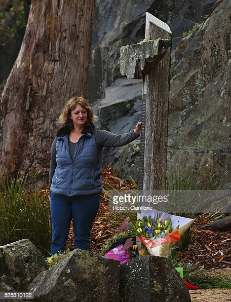 A family member touches the memorial cross during the 20th anniversary commemoration service of the Port Arthur massacre on April 28 2016 in Port...