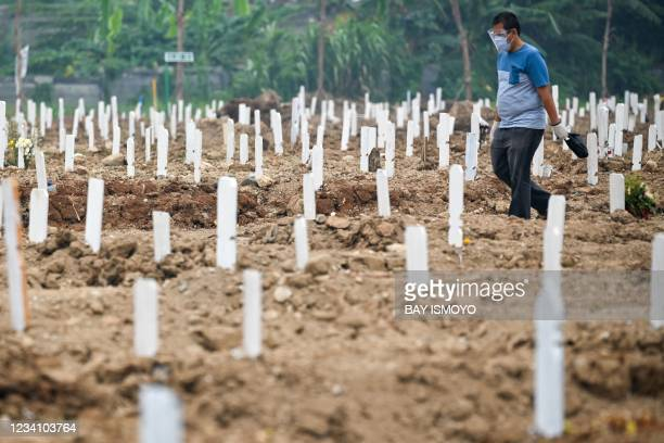 Family member visits his relative's grave at a cemetery for Covid-19 coronavirus victims in Rorotan, Jakarta, on July 22, 2021.