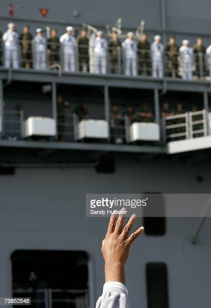A family member waves to marines and sailors aboard the USS Bonhomme Richard as it departed on a six month deployment on April 10 2007 at 32nd Street...