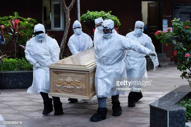 Family member wearing Personal Protective Equipment Kit and caring coffin of Rita Mehra to perform last rituals at Shamshaan BhoomiSantacruz on March...